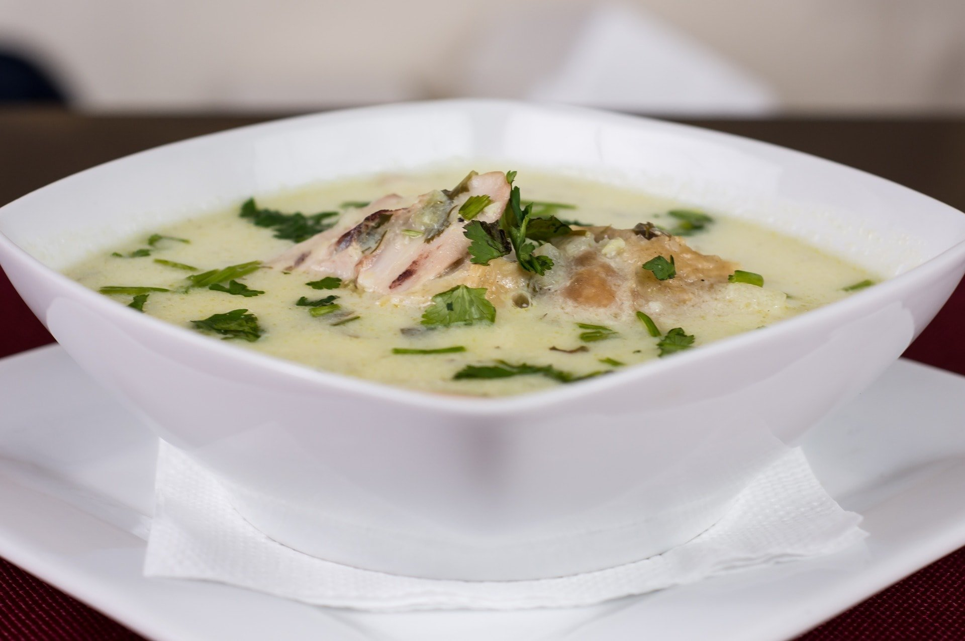 Picture of green chicken enchilada soup in a bowl sitting on a white dish.