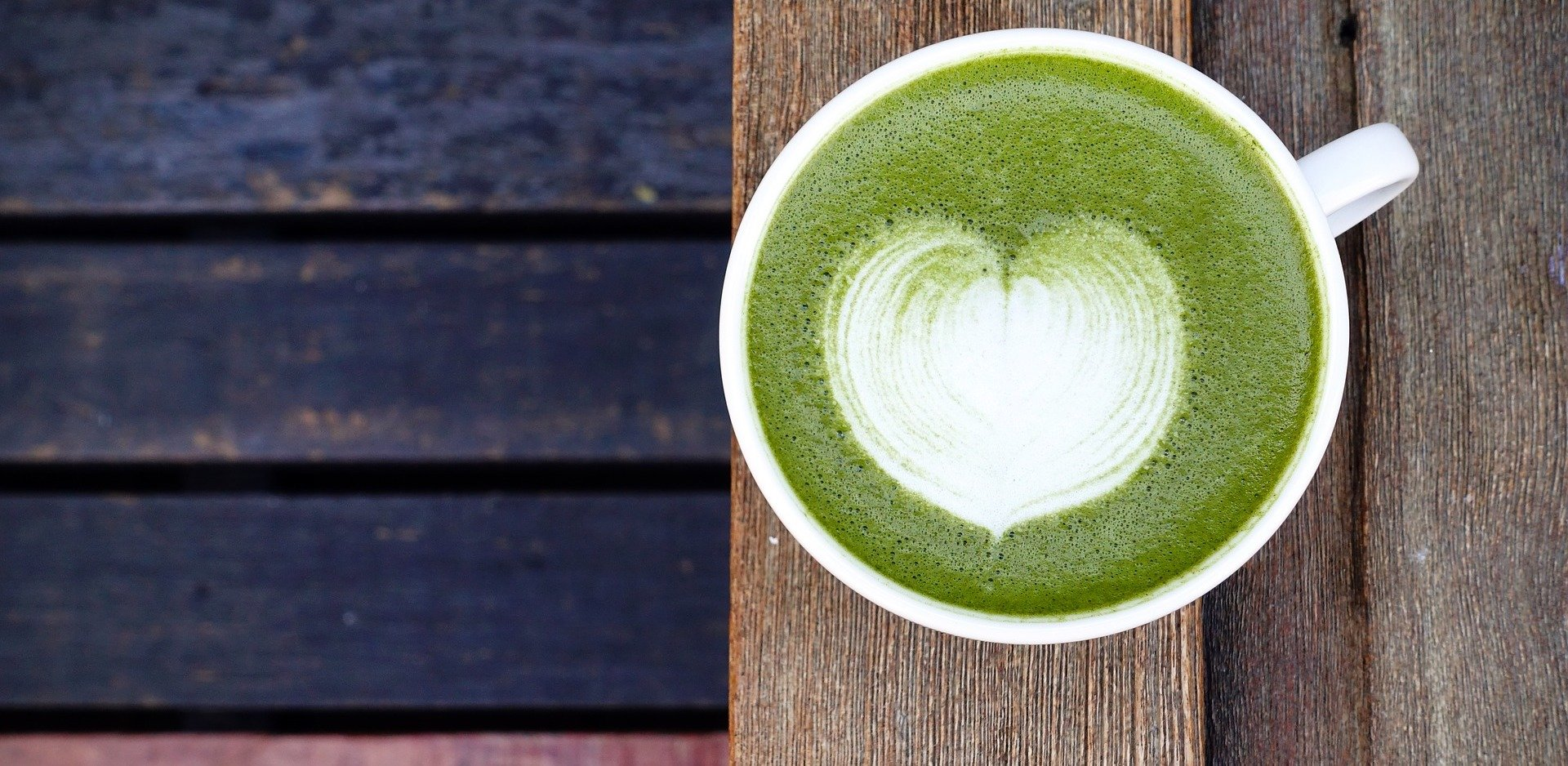 A cup of keto matcha latte with a heart design in its center.