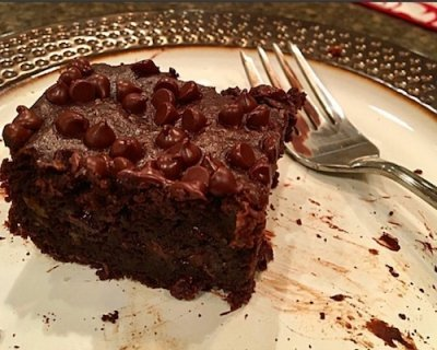 Close up picture of an avocado brownie on a dish sitting next to a fork.