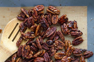 Close up of pecans scatrtered on a place mat.